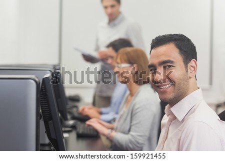 Content mature student sitting in computer class in college smiling at camera  - stock photo
