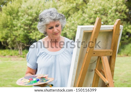 Content mature woman painting on canvas in park
