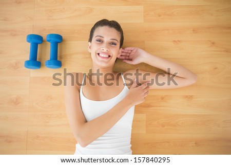 Content natural brown haired woman in white sportswear lying on the floor in bright living room - stock photo