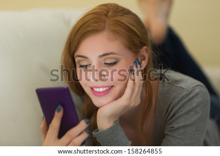 Content redhead lying on the sofa sending a text at home in the sitting room - stock photo