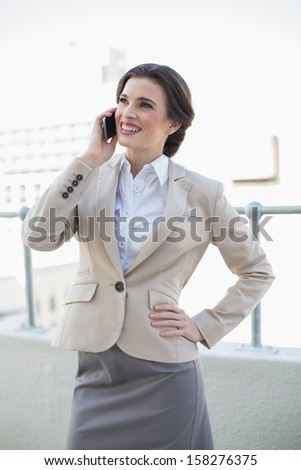 Content stylish brown haired businesswoman making a phone call outdoors - stock photo