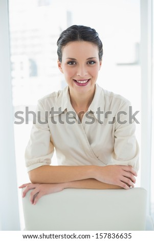 Content stylish brunette businesswoman posing looking at camera in bright office