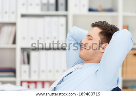Contented businessman taking a break sitting back in his chair at the office with his hands clasped behind his head, eyes closed and a smile of pleasure - stock photo