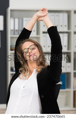 Contented businesswoman stretching her arms above her head with her eyes closed and a satisfied smile - stock photo