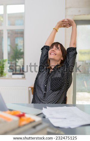 Contented successful businesswoman sitting at her desk in the office stretching her hands above her head with a smile of satisfaction
