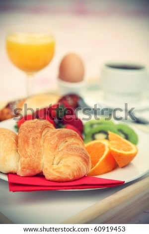Continental breakfast. Breakfast tray on bed with coffee, orange juice, croissant, strawberries, kiwi, bread and egg. Shallow depth of field. - stock photo