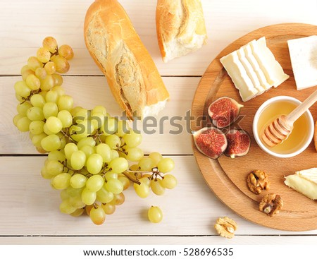continental Breakfast - cheese, honey, figs, walnuts, grapes and baguette on wooden Board - top view