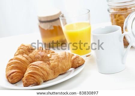 Continental Breakfast, coffee cereals, croissants,honey, orange juice - stock photo