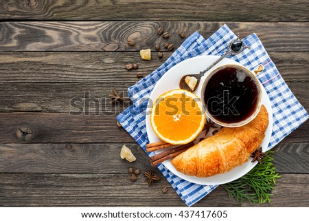 Continental breakfast - cup of hot coffee, croissant and orange. Tasty food on plaid blue napkin. Rustic wooden background. Top view, place for text. - stock photo