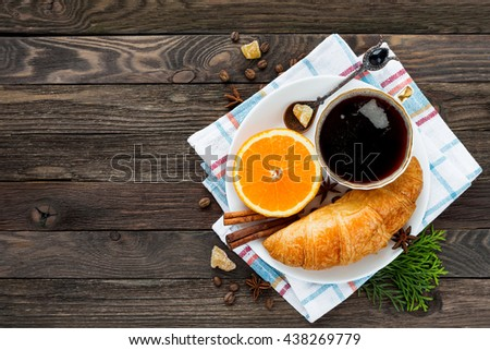 Continental breakfast - cup of hot coffee, croissant and orange. Tasty food on plaid napkin. Rustic wooden background. Top view, place for text. - stock photo