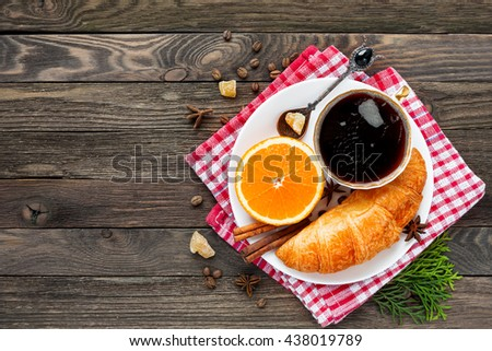 Continental breakfast - cup of hot coffee, croissant and orange. Tasty food on plaid red napkin. Rustic wooden background. Top view, place for text. - stock photo