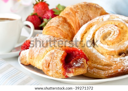 Continental breakfast with assortment of pastries, coffees and fresh strawberries. - stock photo