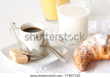 Continental breakfast with coffee, milk, orange juice and croissants served on a table - stock photo