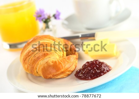 Continental breakfast with croissant, strawberry jam, butter, orange juice and coffee (Selective Focus, Focus on the jam) - stock photo