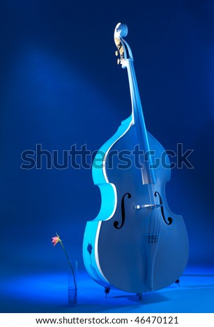 Contra-bass and a rose near it. Mysterious lighting. - stock photo