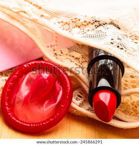 Contraception birth control and safe sex concept. Closeup latex condom and red female lipstick on lace lingerie. - stock photo
