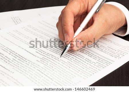 Contract Document signed with hand and pen - stock photo