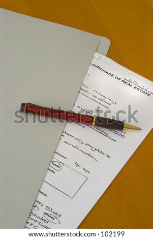 Contract for purchase of real estate, in grey folder, with red pen on top, on wooden desk.