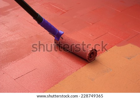 Contract painter painting a floor on color red for waterproofing. He is using a paint roller. - stock photo