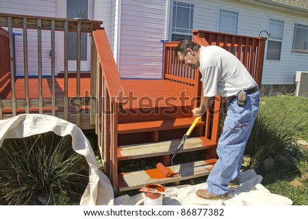 Contract painter staining deck on home to protect it from the weather - stock photo