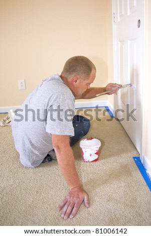 Contract painter updating colors of walls and painting doors,ceilings bright white to speed up selling of home - stock photo