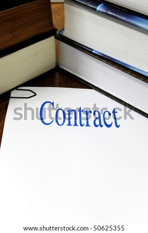 contract with copy space on a desk with stack of books