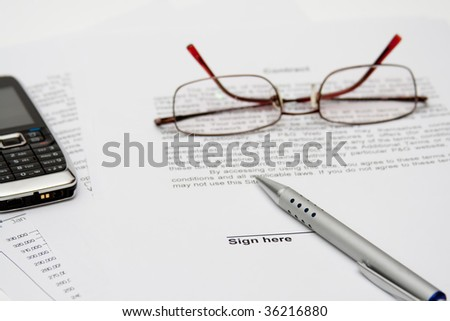 Contract with glasses, cell and pen - stock photo