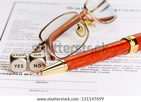 Contract with glasses, pen and dices cubes with words YES NO. Selective focus. conceptual  doubt - stock photo