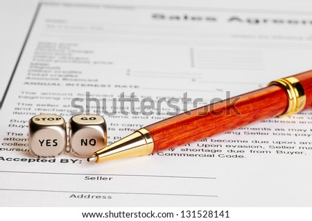 Contract with  pen and dices cubes with words YES NO. Selective focus. conceptual  doubt - stock photo