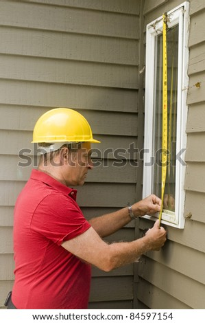 contractor carpenter measuring window for replacement repair - stock photo