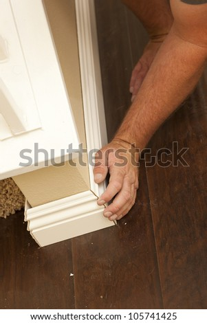 Contractor Fitting New Baseboard to Wall and New Laminate Flooring Abstract. - stock photo