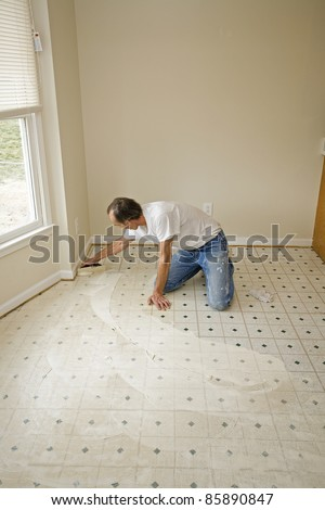 Contractor getting ready to install new kitchen vinyl floor, home is being updated to be sold - stock photo