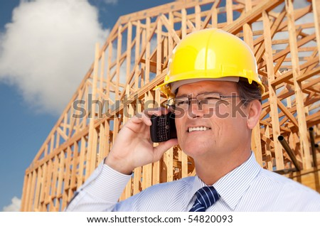Contractor in Hardhat at Construction Site Talks on His Cell Phone. - stock photo