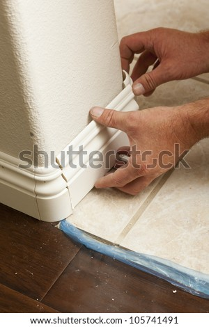 Contractor Installing New Baseboard with Bull Nose Corners and New Laminate Flooring Renovation Abstract. - stock photo