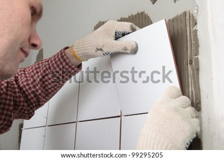 Contractor installing tiles on a wall - stock photo