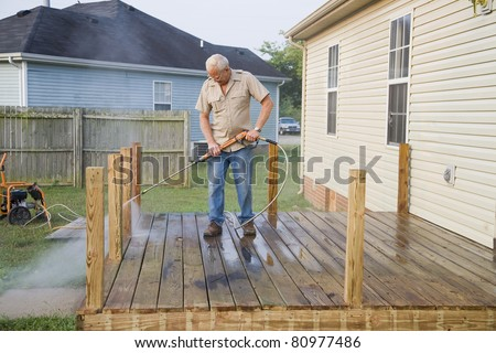 Contractor pressure washing deck , getting home ready to sell - stock photo