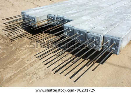 Contractor's lay down area for storage of precast concrete pilings used on a bridge construction project - stock photo
