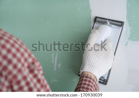 Contractor sanding the drywall mud using sand trowel - stock photo