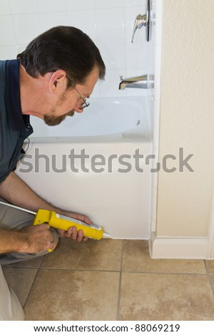 Contractor sealing tub base to keep water from seeping through the ceramic tile and rotting the floor - stock photo