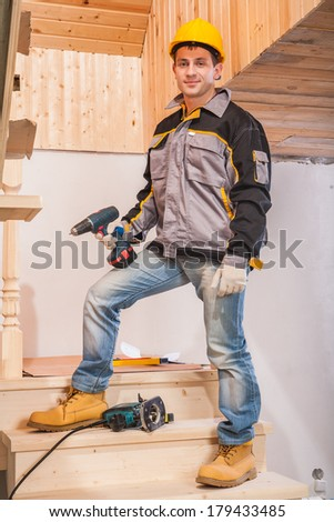 contractor standing on ladder and holding cordless drill