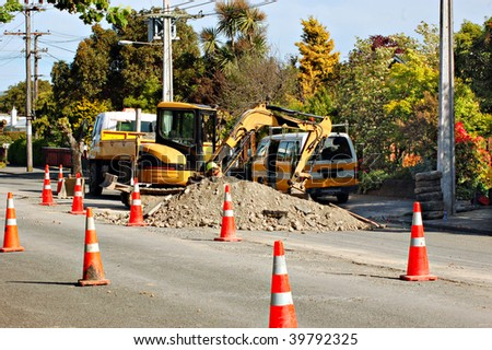 Contractors carrying out street repairs in urban parts of town - stock photo