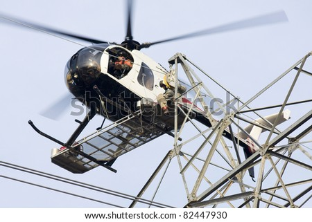 Contractors installing high voltage transmission towers to carry electricity across the country, final work is done with worker sitting on bench below helicopter on the skids making final connections