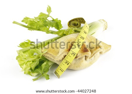 Contradiction between healthy food and junk food using celery and pasty with a tape measure on a reflective white background