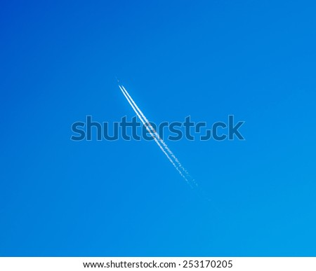 Contrail In Blue Sky. Air plane makes cloud. - stock photo