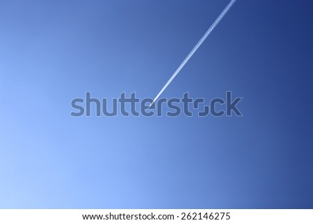 Contrail   straight   to  the  fresh  clear  blue  sky   on   direction  travel   among  atmosphere. - stock photo