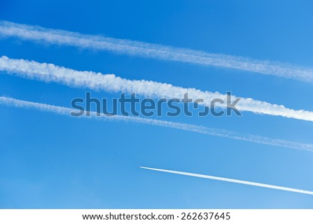 Contrails in the blue sky - stock photo