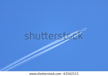 Contrails of a Jet Against a Clear Blue Sky - stock photo