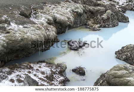 contrast between icicles and warm water in blue lagoon iceland - stock photo
