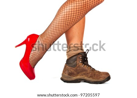 Contrast between two shoes, red high hill and walking boots - stock photo