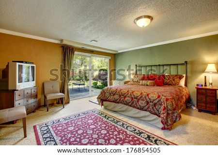 Contrast color bedroom with walkout deck. Room furnished with antique iron frame bed, nightstands, cabinet with tv and old fashioned chairs. - stock photo